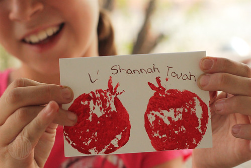 Girl holding a handmade L' Shana Tovah! card with a picture of pomegranate