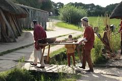 Christian Timm und Wulf Freese tragen einen Tisch über die kleine Brücke bei den Wikinger Häuser in Haithabu – Museum WHH 16-09-2011