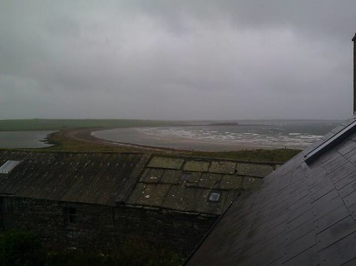View from a second-floor window on a heavy, stormy sky over an old stone barn and a curved coastline, on Shapinsay, Orkney Islands