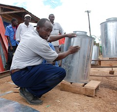 Workshop on making metal silos for grain storage, Kenya (CIMMYT) Tags: africa man metal training corn technology kenya african working storage silo demonstration workshop taller impact teaching agriculture showing making atwork partnership maize kenia partner collaboration hombre artisan trabajando manufacture kenyan africano tecnologa demonstrating asociacin eastafrica impacto agricultura explaining sdc fabricando enseando frica artesano mostrando maz colaborador capacitacin demostracin colaboracin subsaharanafrica collaborator explicando fabricacin almacenamiento enseanaza foodsecurity asociado demostrando cimmyt eneltrabajo almacenaje seguridadalimentaria keniano incomesecurity fricaoriental fricasubsahariana swissagencyfordevelopmentandcooperation effectivegrainstorage almacenamientoefectivodegrano postharvestlosses prdidasposcosecha seguridadeconmica