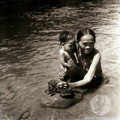 JE47-24-11-1956 (Christine Horn) Tags: portrait people river children outside others community traditional objects location clothes daytime subject earrings 1956 date bathing oldpeople riverbank washing sarong activities timeofday tinjar womanone