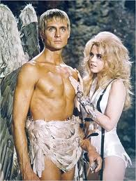 jane fonda as barbarella looking coyly at pygar, the shirtless blonde angel wearing a feathered loincloth