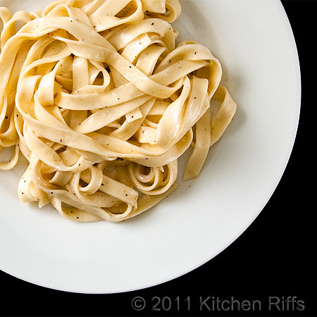 Fettuccine Alfredo on white plate, black background, off center overhead view