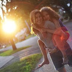 Evening sun (Martyn Russell) Tags: sunset portrait sun tree love smiling 50mm nikon hug warmth lensflare barefoot f18 curlyhair piggyback greytshirt denimshorts nikond3