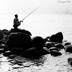 Patiently waiting for his prey #2. (Reggie Wan) Tags: seascape man fishing singapore asia southeastasia rockybeach punggolbeach reggiewan sonya850 sonyalpha850 gettyimagessingaporeq1
