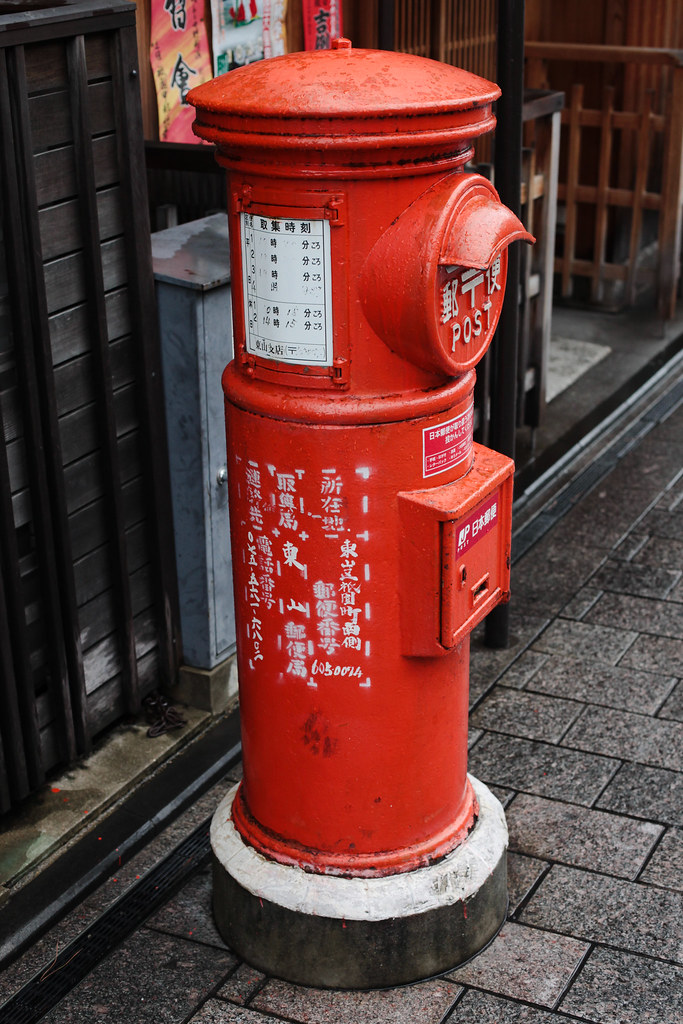 Bright red cylindric mailbox in Kyoto on a rainy day