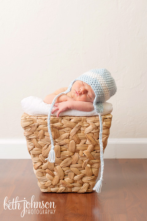 baby boy in blue and white hat in little basket