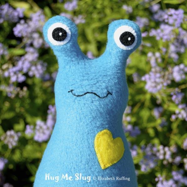 Turquoise fleece Hug Me Slug with a bright yellow heart by Elizabeth Ruffing