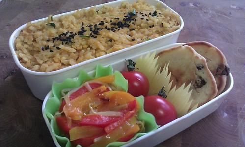 Op de foto staan 2 beige bakjes. In de grootste zit geel-kleurige rijst met gele linzen en gehakte verse koriander. In het midden liggen zwarte nigellazaadjes in een lijntje. Het kleine doosje heeft een siliconen cup die er uit ziet als een bakje van sla, met daar in roergebakken paprika in drie kleuren en taugé. Daarnaast zitten 2 cherrytomaten met steeltje tegen een gele gras-'baran' die de tomaatjes apart van de 2 mini 3-in-de-pan pannenkoekjes houdt.