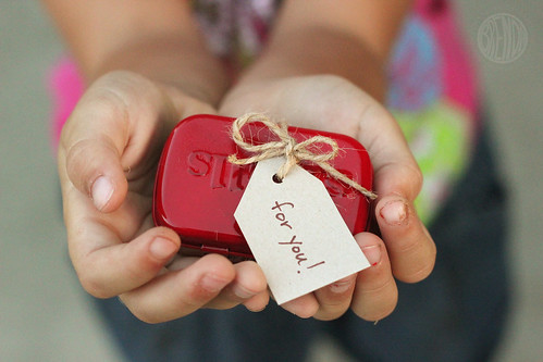 red painted small Altoid can with twine and a gift card in a child's hands