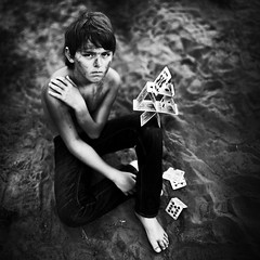 the only home ive ever known, and its a fragile one indeed. (karrah.kobus) Tags: boy portrait blackandwhite cards alone child dirty fragile cardhouse