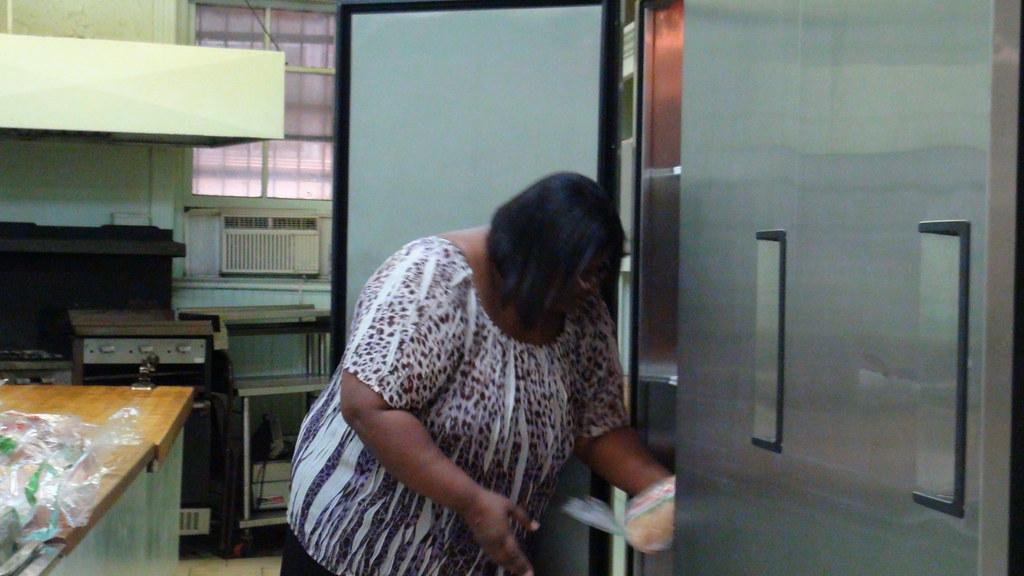 Ericka Ward putting bread in the refrigerators