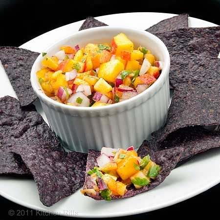 peach salsa in white ramekin on white plate with blue corn chips, black background