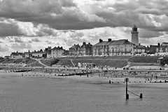 Oh I Do Like To Be By The Sea Side (Susie Potter) Tags: houses sea people blackandwhite lighthouse beach water clouds sand pylons beachhuts