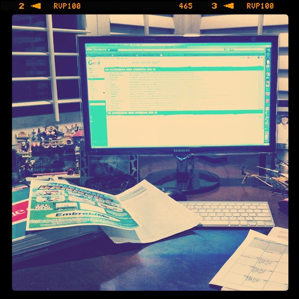 Chaos on the desk: email, calendars, soccer paperwork.