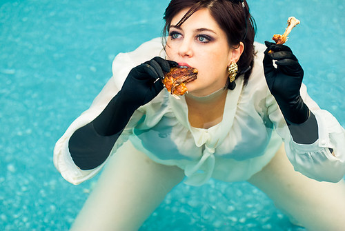 Nancy, a white woman, wears fancy clothes and eats chicken in a pool