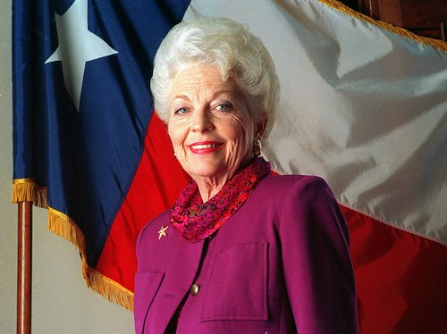 Governor Ann Richards, a white woman with white hair, stands in front of the US flag