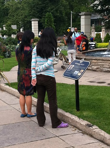 tourists reading the Casa Loma plaque