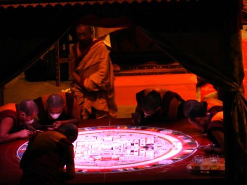 Artist monks working on completing the sand Kalachakra mandala inside the pavilion, stage, Kalachakra for World Peace, red light during a lighting change, Verizon Center, Washington D.C., USA by Wonderlane