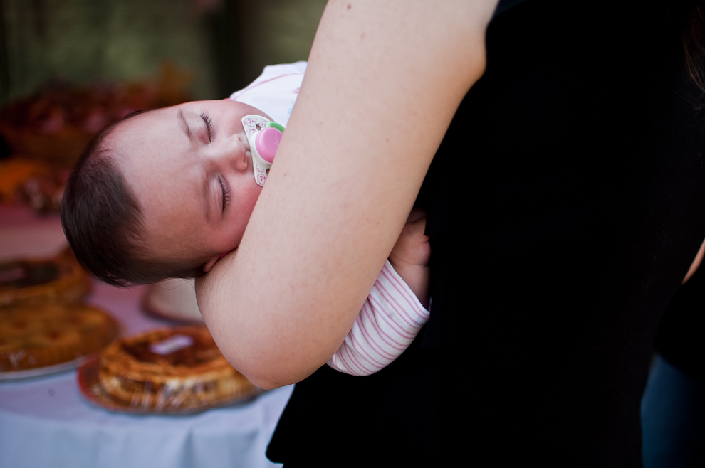 Una bebé duerme en los brazos de su madre mientras ella compra los postres exhibidos en uno de los stands del festival. (Elton Núñez)