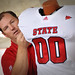 An equipment manager adjusts a display jersey before the crowd enter Carter-Finley for Meet the Pack.