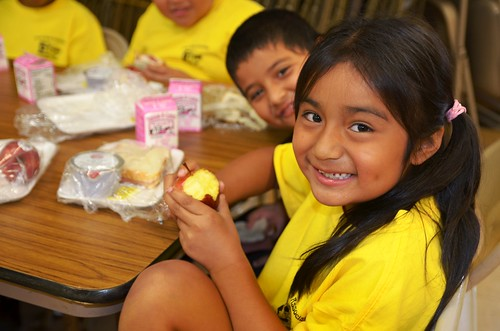 A youngster enjoys a crisp apple for lunch at the Puerto Rican Association for Human Development's Mi Escuelita summer food program site in Perth Amboy, New Jersey.   More than 75 kids enjoy physical activities such as soccer and basketball followed by a free healthy lunch each day during summer thanks to the USDA Summer Food Service Program.