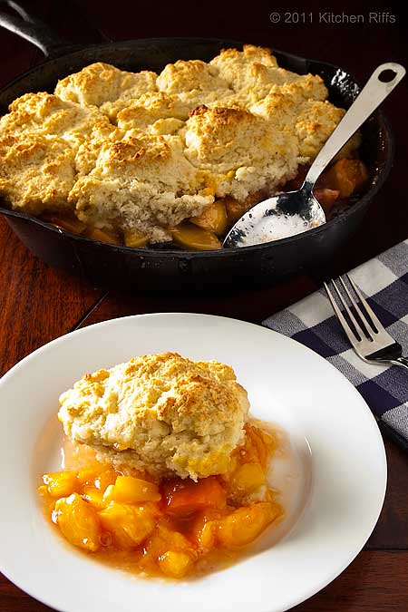 peach cobbler on plate with cobbler in cast iron skillet in background