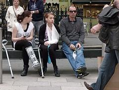 The Front Line (Andy WXx2009) Tags: girls woman men sunglasses wales shopping bench funny europe sitting cigarette candid femme capital cardiff injury streetphotography plaster smoking sling bandage crutch brokenarm crosslegged footinjury mygearandme