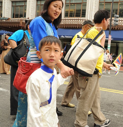 A Tibetan woman (turquoise chuba, blue blouse) & son (traditional white & blue silk shirt), entire families marching, Tibetan national flag, Happy Birthday to His Holiness the Dalai Lama Peace Parade, Tibetans at Kalachakra, Washington D.C., USA by Wonderlane