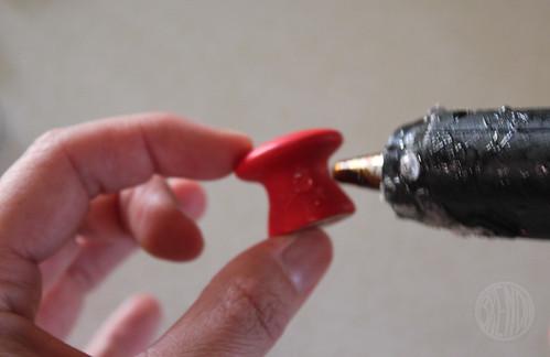 hot glue gun adding glue to red painted wooden knob