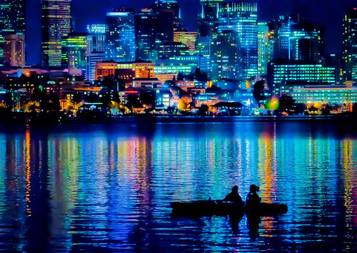 night scene of a brightly lit city scape and water, with two people in a boat