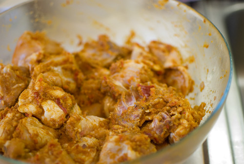 Chicken marinating with curry paste and ground aromatics