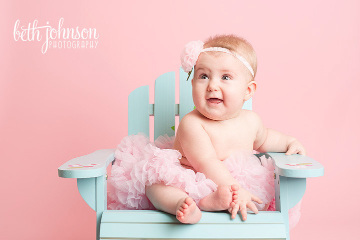 six month old baby girl in beach chair pink background