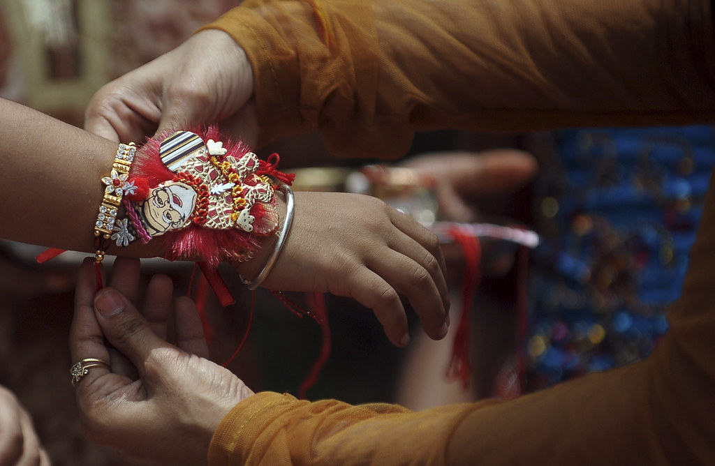 Tying rakhi around a brother's wrist