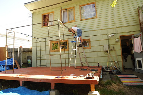 Mike constructing the wire frame for a gazebo, standing on a ladder, above the fresh deck, backyard, back door, carpet, windows, Broadview, Seattle, Washington, USA by Wonderlane