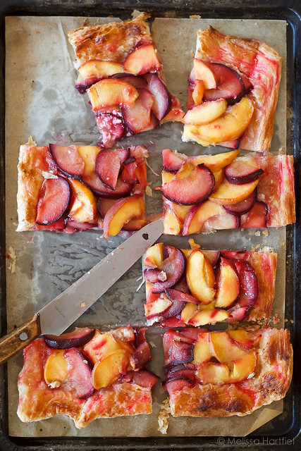 Rustic Peach Plum Tart sliced in pieces in the pan