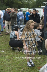 Chav gypsy girl wearing a Burberry style matching check cape and shirt. (Homer Sykes) Tags: uk england english girl children child britain travellers september british gypsy gypsies chav hertfordshire barnet burberry gbr horsefair annualevent bestclothes teenteenager travelstockuk
