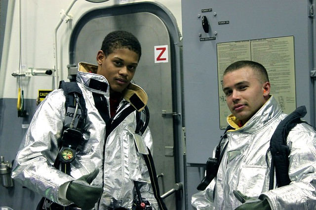 BMSN Lomack and MR2 Limon get ready to fight an aircraft fire onboard USS SPRUANCE (DDG 111) in Bath, Maine.