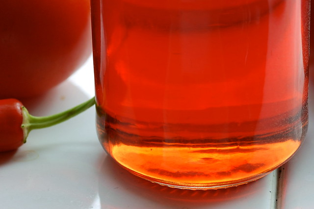 Light shining through a jar of red crabapple jelly on a windosill