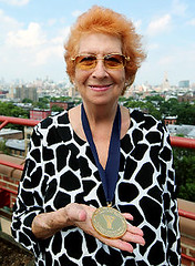 Kanokogi as an older woman holding a gold medal