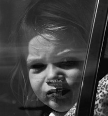 Backseat Passenger (Cheryl Atkins) Tags: street cute girl car glare child candid backseat drivebyshootings windowsticker