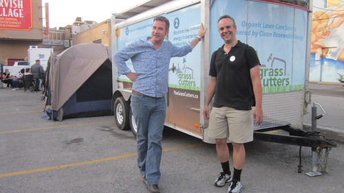 RobC and JimP stand beside the solar panels of the Grasscutters trailer in Toronto