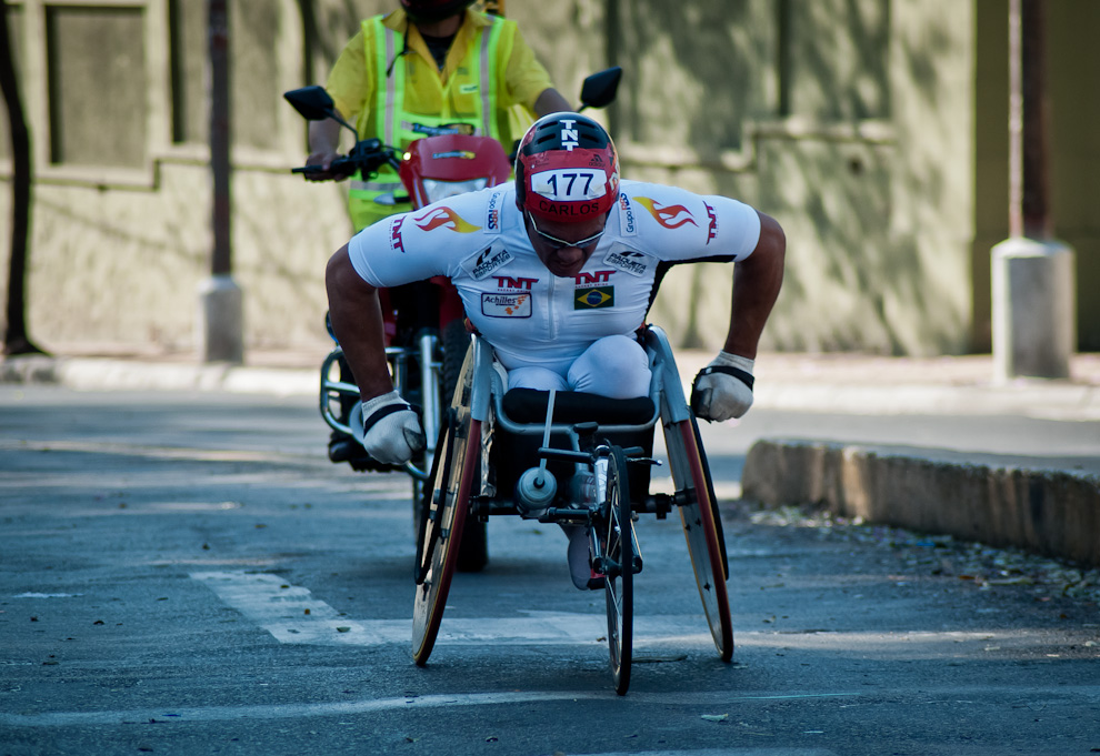 Carlos Oliveira avanza sobre la Avenida Mariscal López en su silla de ruedas equipada especialmente para competencias, culminó la categoría 42km en 02:09:30. El espíritu del Maratón admite a toda clase de personas sin importar la edad o impedimento físico. (Elton Núñez)