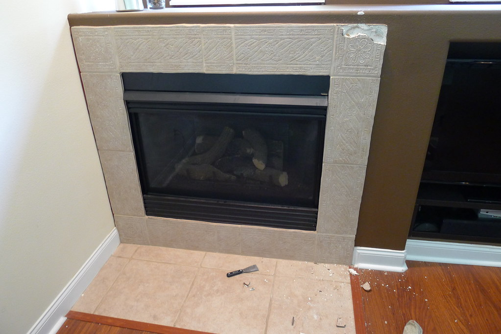 I am currently working on removing the tile from around this Heatilator brand gas fireplace. Here is a before photo: I have started removing the old tile using a multi-tool to cut the drywall out. Those things work great! Well