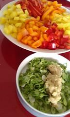 Twee borden: één met zes paprika's in drie kleuren; geel, rood en oranje en één met fijngesneden bosui en geraspte gember. Eén paprika van iedere kleur is in blokjes gesneden en de ander in reepjes.