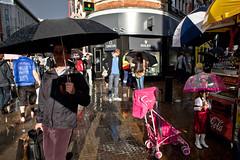 Sunlight in the rain (Gary Kinsman) Tags: oxfordstreet w1 london canoneos5dmarkii canon5dmkii canon28mmf18 candid streetphotography streetlife umbrella sun light holdtight man shadow littlegirl reflectedlight 2011 people person