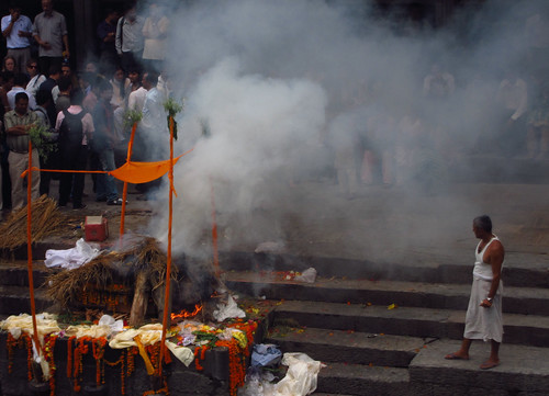A ghat attendant at Pashupati monitors the cremation