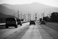 steel blades on the walls of time (Super G) Tags: blackandwhite bw mountains west cars windmill pavement trucks interstate donquixote sanchopanza interstate10 weirdthingsisee ofthe21stcentury inmybwworld outsidecabazon