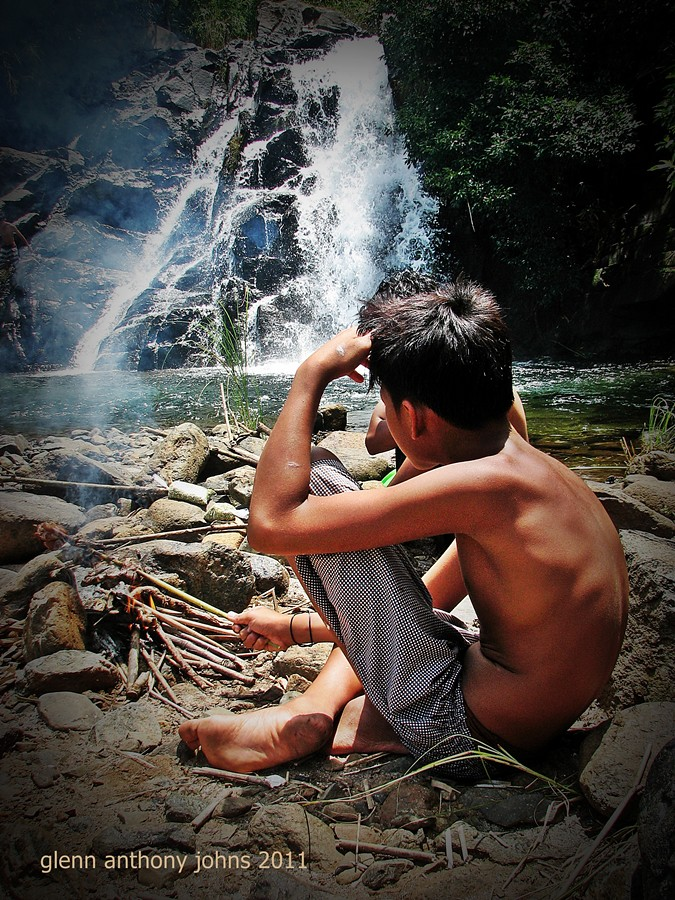 Boy Cooking Chicken on Open Fire at Waterfall