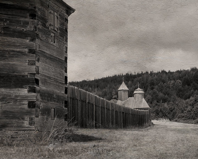 This is a textured and aged sepia photograph of Fort Ross.